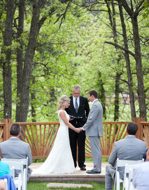 bride groom and officiant at wooded outdoor wedding