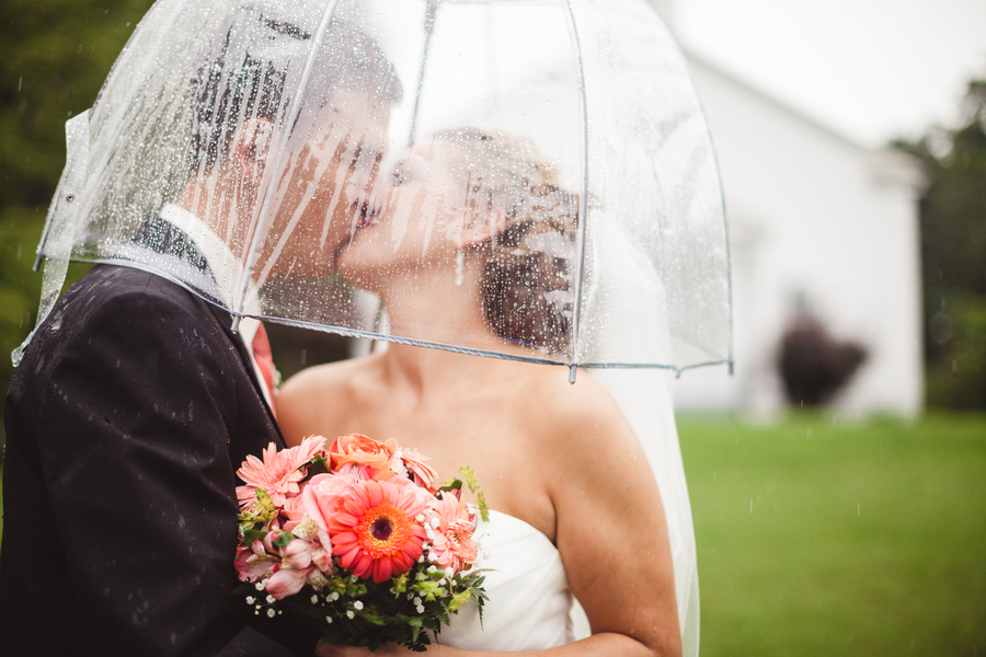 bride and groom kiss in rain
