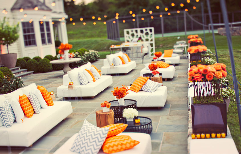 Orange and white furniture with candles, flowers and lights