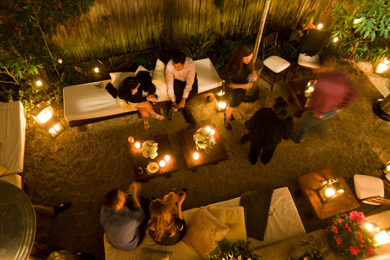outdoor seating area with candles, flowers and people