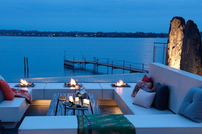 outdoor lounge with couches and fire pit on the water