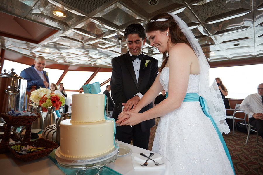 Newlywed couple slicing wedding cake