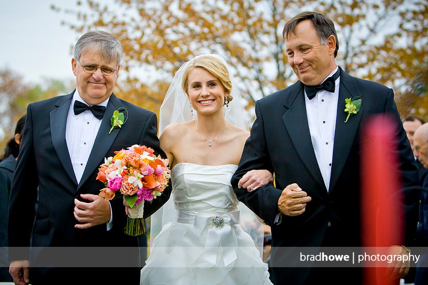 bride walks down aisle with two fathers