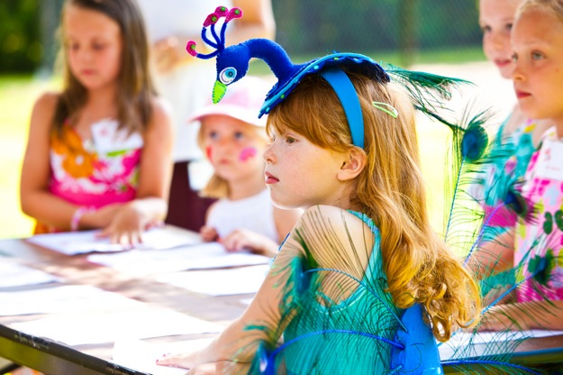 red haired girl in outrageous peacock tea party hat