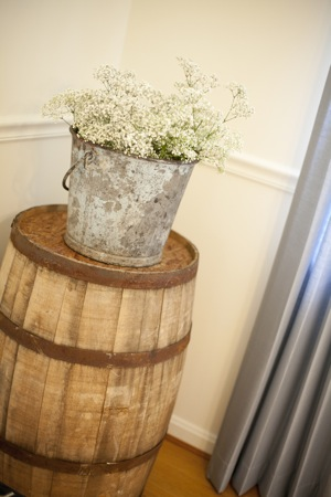 vintage pail of flowers on display on top of barrel