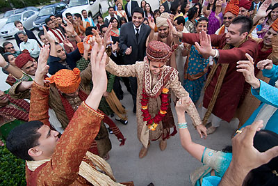 Hindu groom dances in the street at his Indian wedding