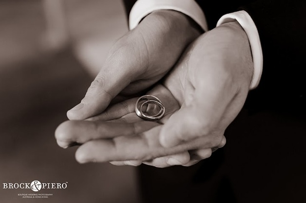 groom holding gold rings