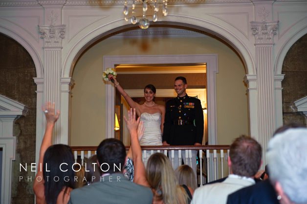 bride in strapless dress and groom in uniform on balcony