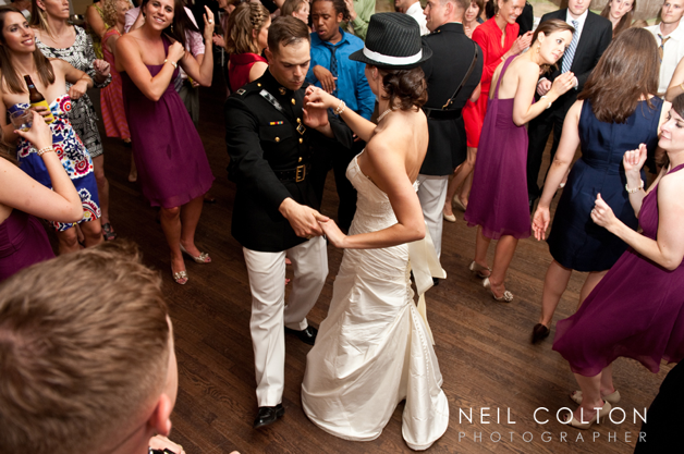 bride in fedora dances with groom
