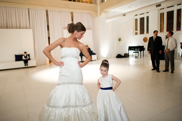 bride in strapless dress dances with flower girl in white dress