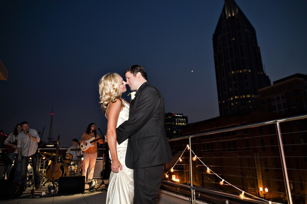 couple on roof top embrace after wedding