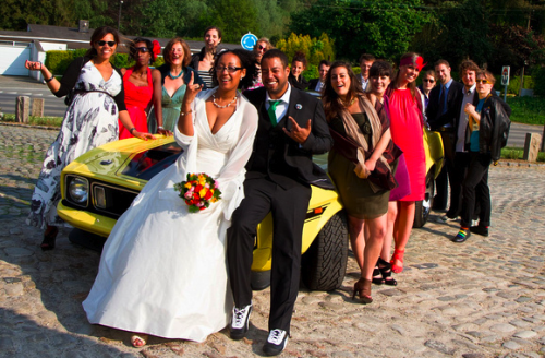 yellow car with bridal party leaning on it