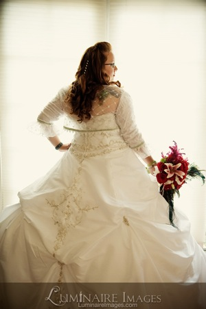 bride in full white ballroom gown from back