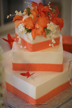 orange flowers and trim on three tiered white wedding cake