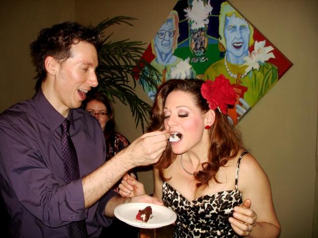 groom feeds cake to bride