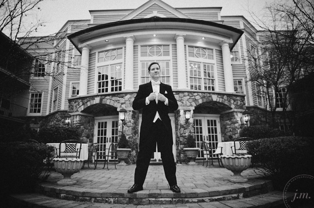 groom stands in front of house