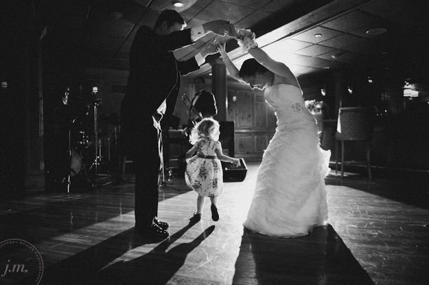small child dances with bride and groom