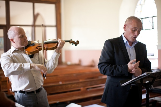 singer and violinist play at church wedding