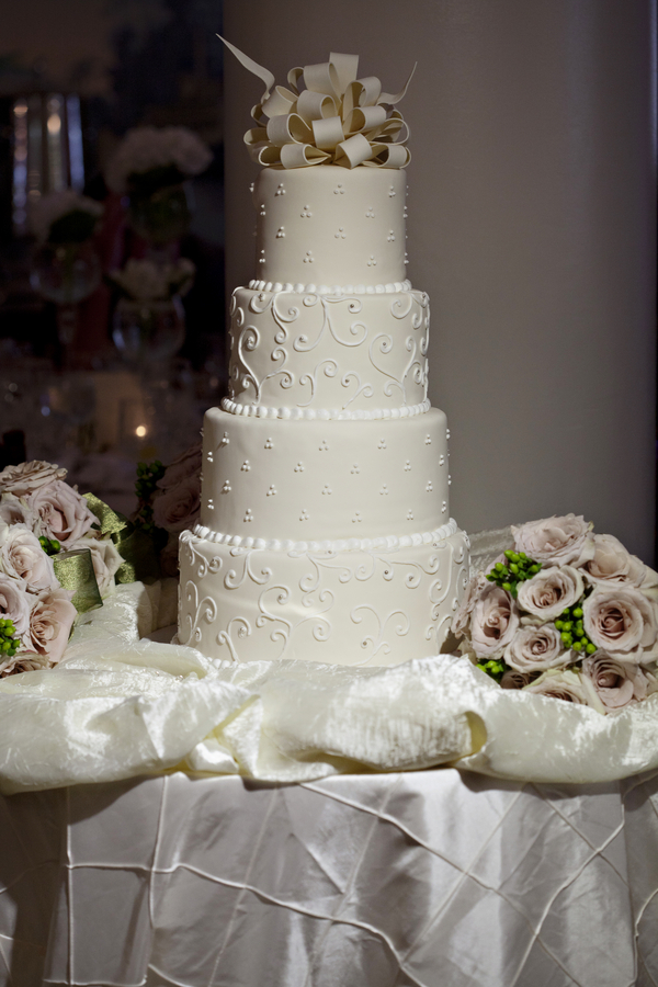 intricate designs on four tiered white wedding cake