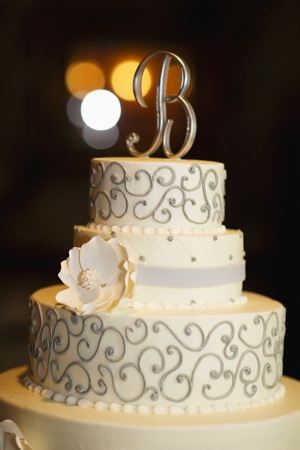 silver scrolls on three tiered white cake