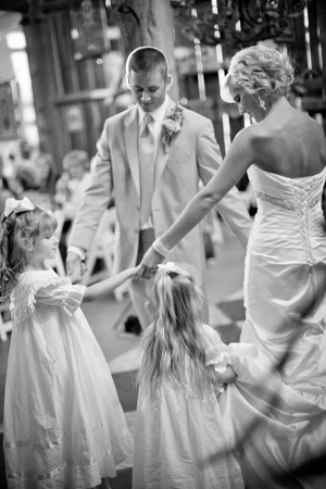 bride and groom dance with kids at wedding