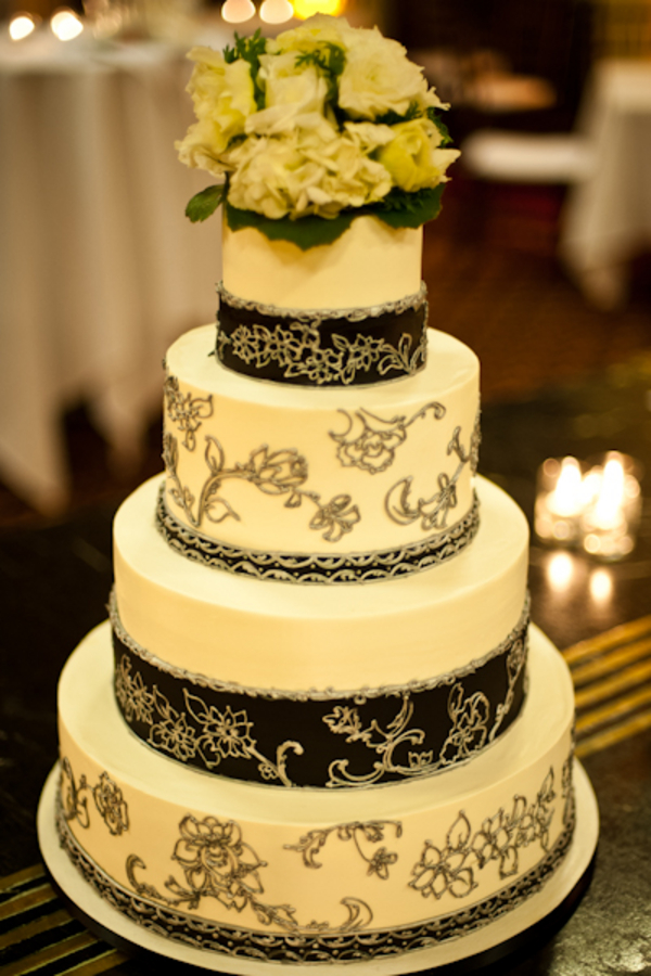 dramatic four tiered wedding cake with black ribbons