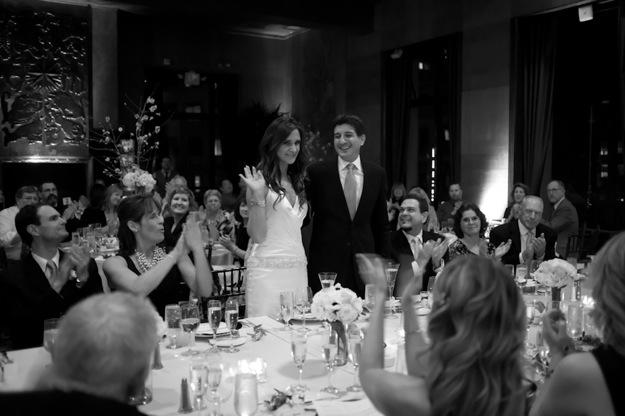 bride waves at wedding reception
