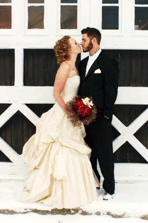 bride with red bouquet kisses groom outside