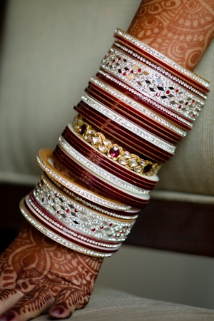 bride's arm decorated with henna and bangles