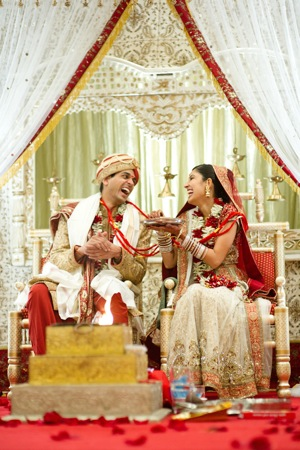 Indian bride and groom sit on chairs