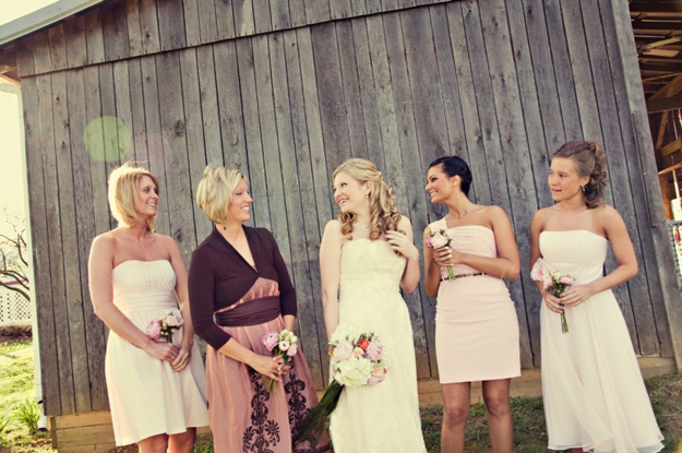bride and bridesmaids in various length dresses at barn