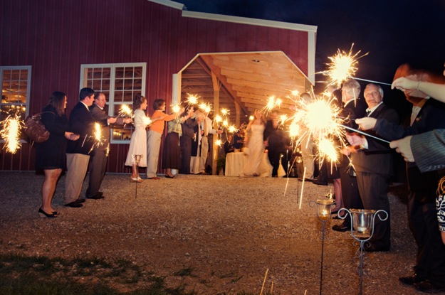 bride and groom leave barn wedding with sparklers