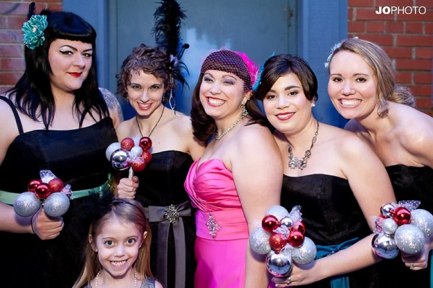 bride in pink dress, bridesmaids in black