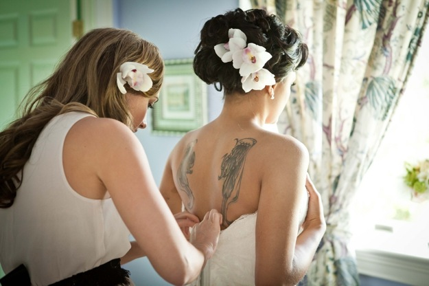 tattooed bride has dress zipped