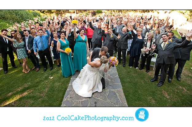 bride and groom kiss in front of entire wedding party