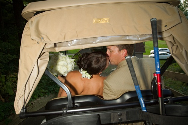 groom kisses bride in golf cart