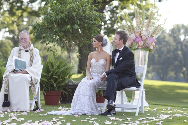 bride and groom sit outside at ceremony