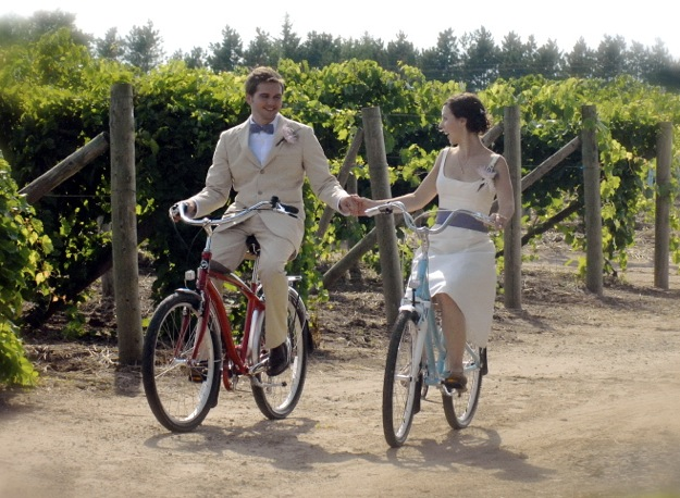 bride and groom on bicycles in vinyard