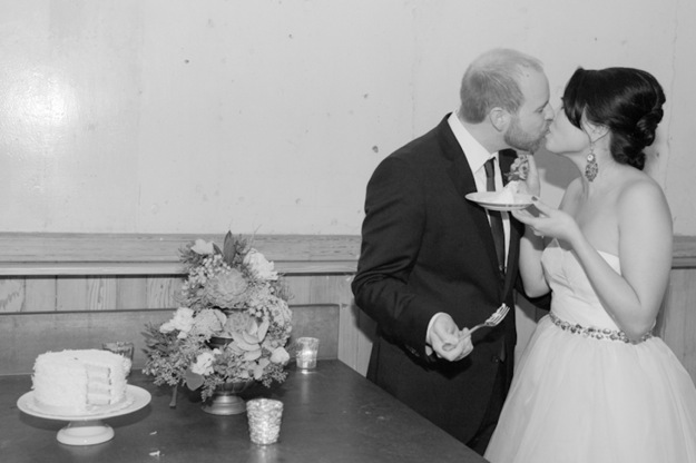 bride and groom kiss after eating wedding cake
