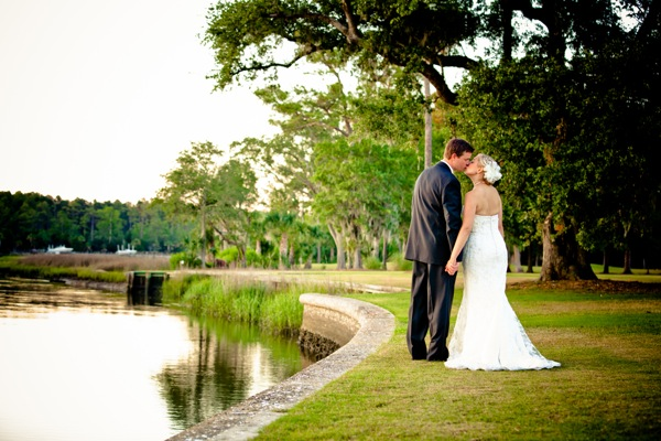 groom kisses bride by lake