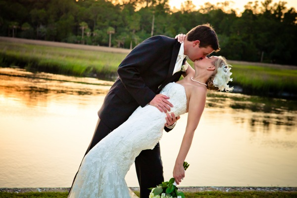 groom and bride share kiss by lake