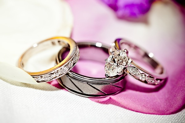 wedding rings and diamond engagement ring resting on purple flower petal