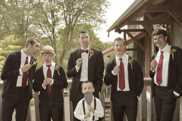 groom and groomsmen with photo booth props