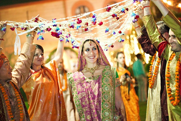 bride at Indian wedding walks under flowers
