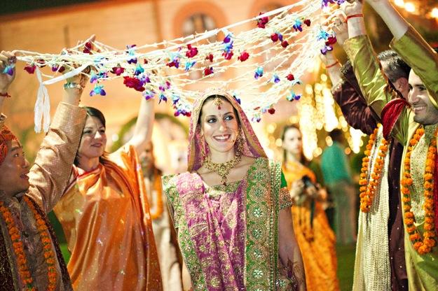bride at Indian wedding walks under flowers