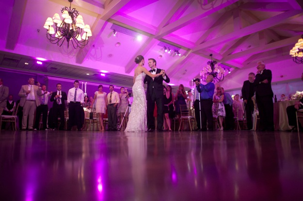 bride and groom dance in pink lighting