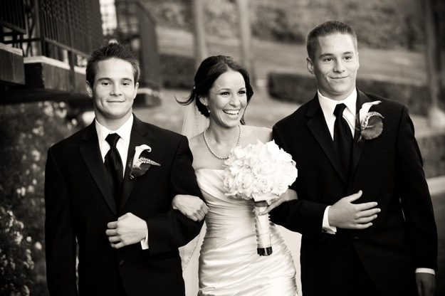 bride and teenage sons walk down the aisle