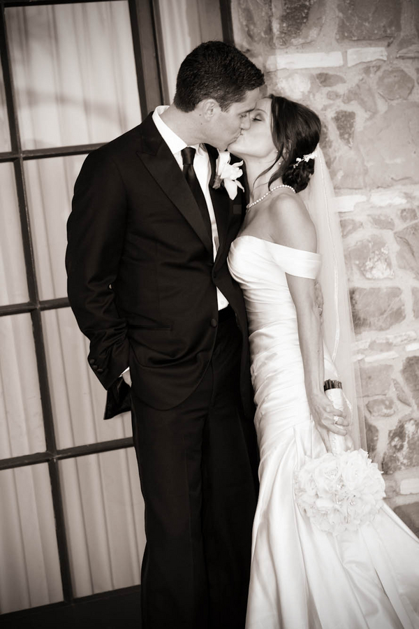 bride and groom kiss at door