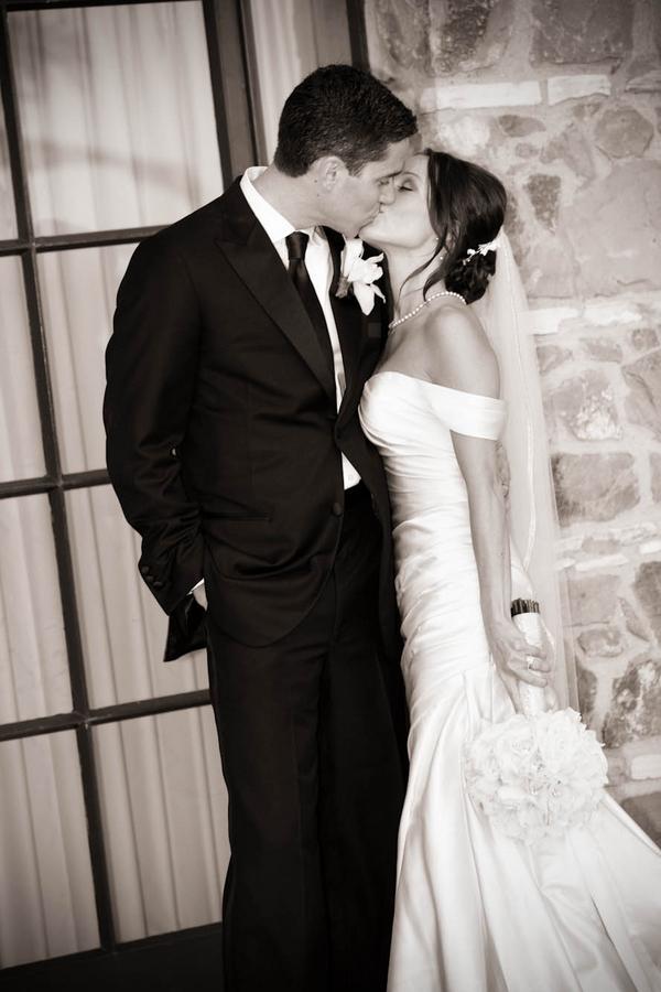 bride and groom kiss at door