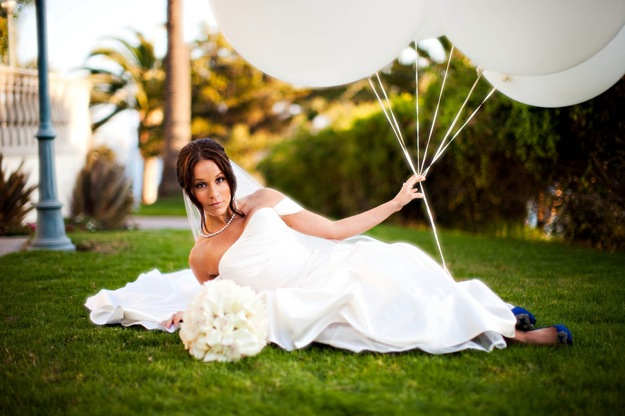 bride in white dress on grass with white balloons